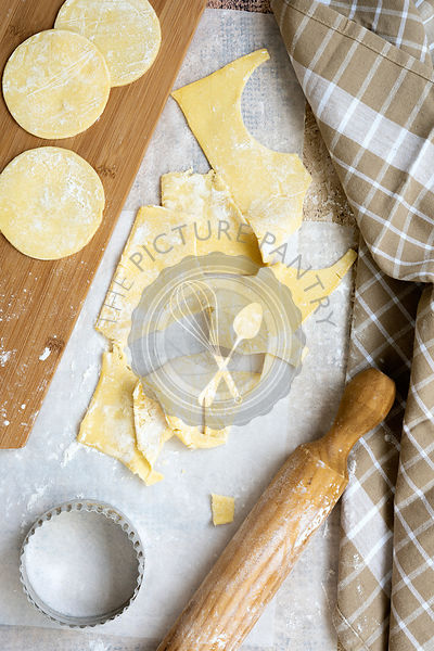 Round circles of shortcrust pastry with leftover pieces beside a rolling pin and bisuit cutter.