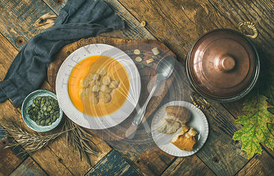 Fall warming pumpkin cream soup with croutons and seeds on board over rustic wooden background, flat-lay
