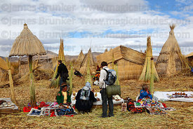 Tourists looking at souvenir stall , Uros floating reed islands , Lake Titicaca , Peru