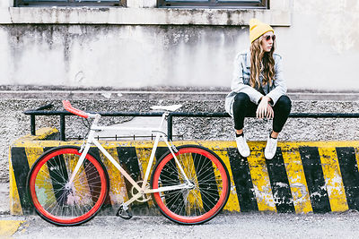 Fashionable young woman with bicycle sitting on railing