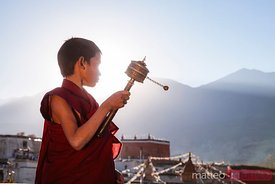 Novice monk spinning prayer wheel, Upper Mustang, Nepal