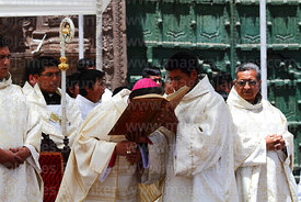 Bishop of Puno Jorge Carrion Pablisch kissing bible after reading from it during central mass, Virgen de la Candelaria festival, Puno, Peru