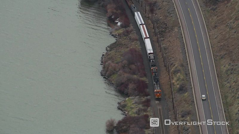 Aerial view of train moving down tracks parallel to roadway