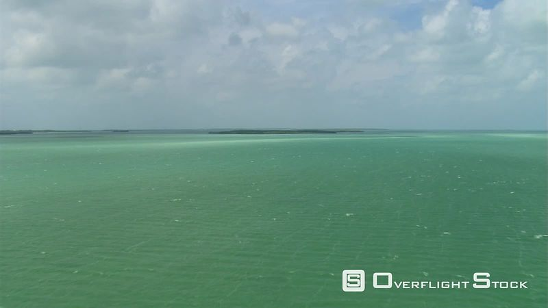 Flight over green water toward low-lying island on Florida coast