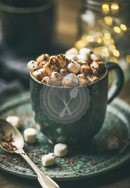 Winter warming sweet drink hot chocolate with marshmallows and cocoa in mug with Christmas holiday lights behind
