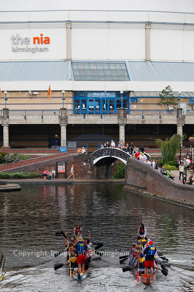Dragon boat racing in Brindleyplace, Birmingham, showing the National Indoor Arena.