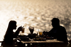 An unidentified man and woman in silhouette at an outdoor seaside restaurant.