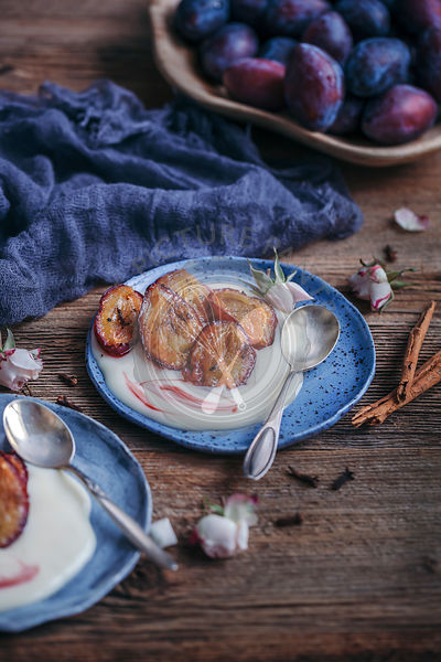 Roasted plums served with coconut yogurt on dessert plates