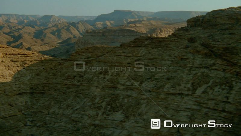 Aerial shot side of weathered rock formation and at gap wide angle of mountain ranges with partial river and desert sand below Fish River Canyon Namibia