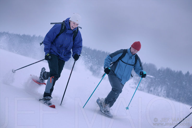 Couple running with snowshoes