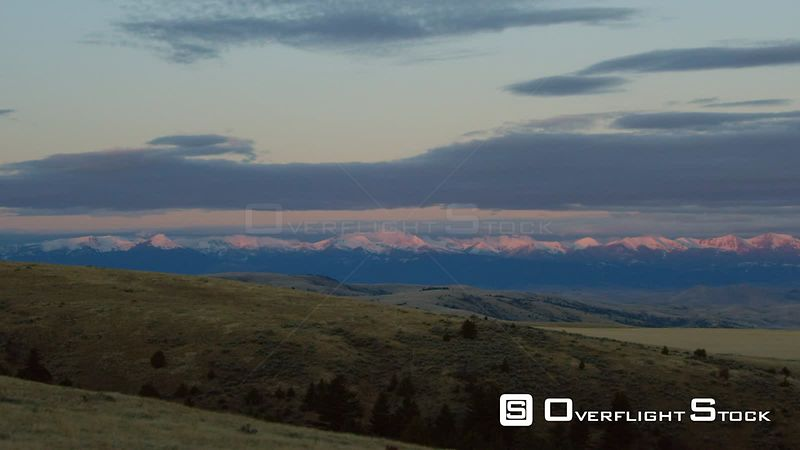 The early morning sunrise highlights the snow-covered peaks of the Tobacco Root mountains, beneath the setting full moon near Bozeman, Montana
