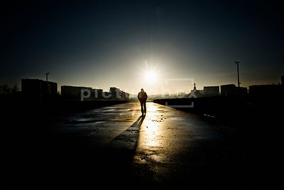 An atmospheric image of the silhouette of a hooded mystery man, walking away, in an empty car park on a housing estate.