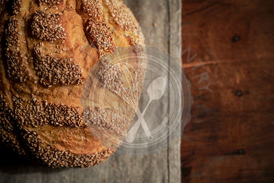 Round loaf or rustic, seasme bread on a linen and rich, wood surface.