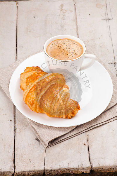 breakfast with croissants, cup of coffee and milk