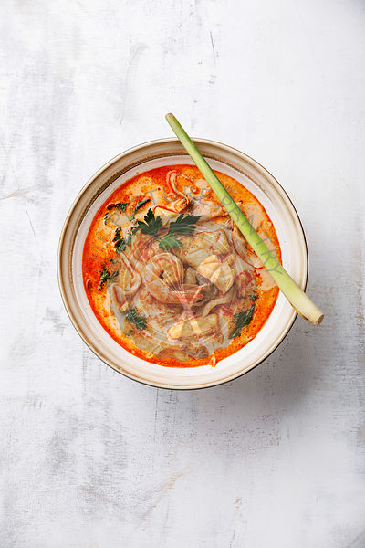 Tom Yam kung Spicy Thai seafood soup with shrimp, coconut milk and lemon grass in casserole dish