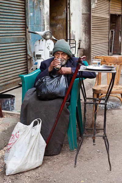 Egypt - Cairo - An old man drinks a cup of tea outside a coffee-house in the Bein al-Qasreen area, Islamic Cairo