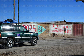 Toyota Land Cruiser driving past propaganda showing support for Evo Morales and the industrialisation of the Salar de Uyuni's lithium reserves, Colchani, Bolivia