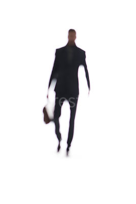 A abstract blurred figure of a man carrying a case – shot from mid level.