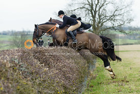 Louisa Fear and Sasha de Gale jumping a hedge near Wilson's covert