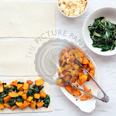 Preparation of roast pumpkin, spinach and feta cheese tarts with bowls of ingredients.