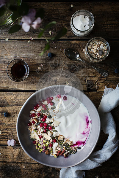 Breakfast on wooden table: yogurt with oat flakes, seeds, pistachios, hazelnuts and currants. Top view