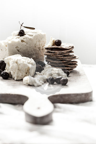 Feta, olives and crackers on white cutting board