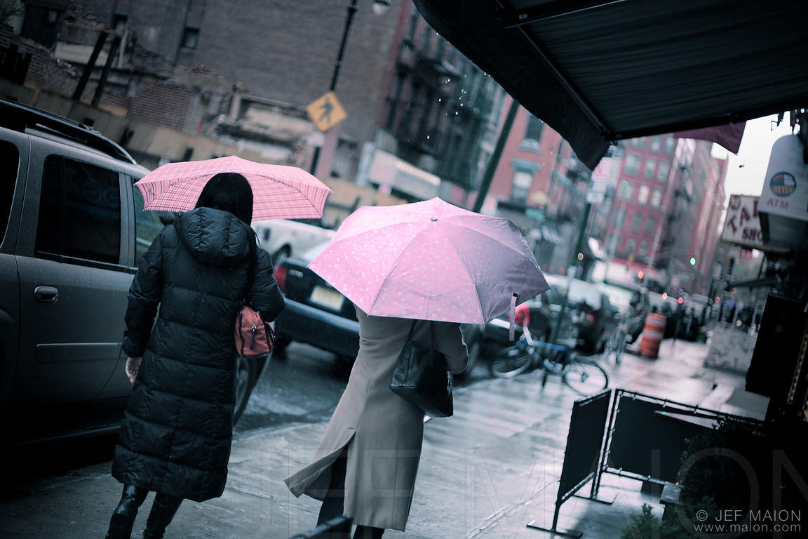 Women walking in rain with pink umbrella