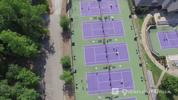 Multiple Tennis Courts with Players at a Fitness Club