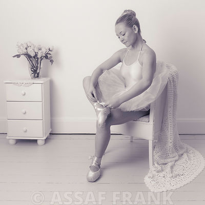 Young ballerina sitting on chair preparing for her performance