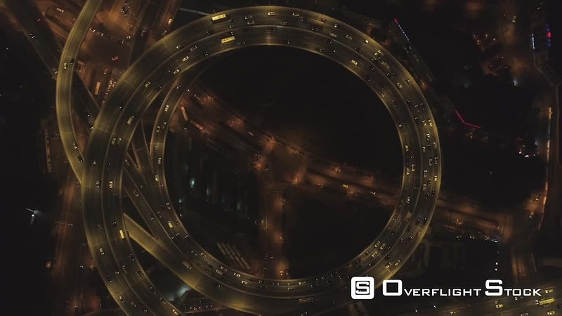 Spiral Illuminated Elevated Nanpu Highway at Night. Shanghai, China. Aerial Vertical View. Drone is Hovering and Spinning Around. Establishing Shot.