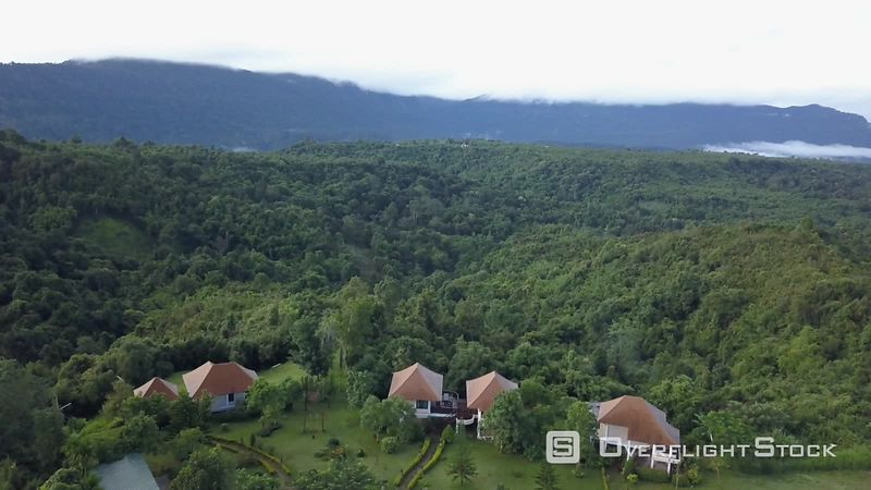 A hotel surrounded by mountains covered by jungle on the Boloven plateau, filmed by drone, Champassak Province, Laos