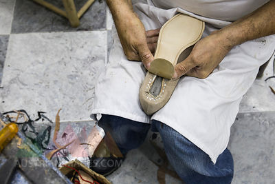 Shoemaker putting the sole on a shoe in his workshop
