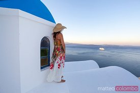 Woman looking at mediterranean sea from blue domed church, Oia, Santorini, Greece
