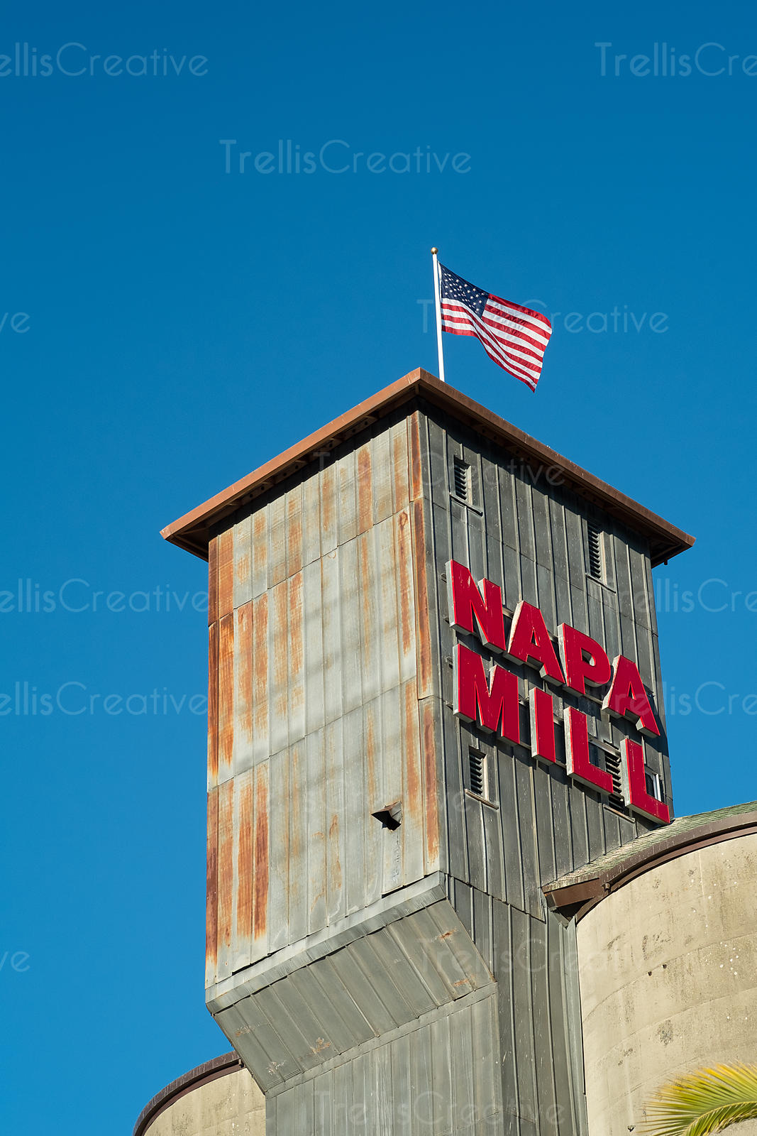 Napa Mill standing tall against the clear blue sky with the American flag flying majestically on top