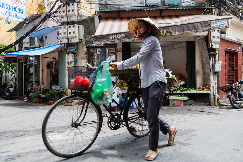 Woman Wearing Traditional Hat Pushing Bicycle