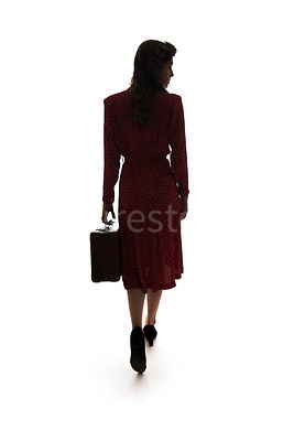 A silhouette of a 1940's woman in a red dress, walking away, with a suitcase – shot from eye-level.