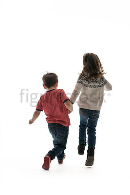 A little girl holding hands with a boy and running away – shot from mid level.