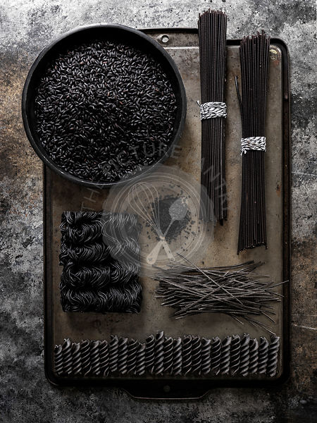 A geometric layout of black pastas (rice, spaghetti, ramen, etc…) on a dark metal surface with a lot of texture and drama
