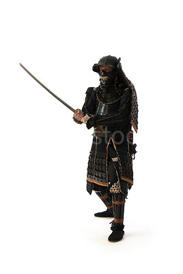 A silouette of a western, Samurai warrior with his sword in the air - shot from mid-level.