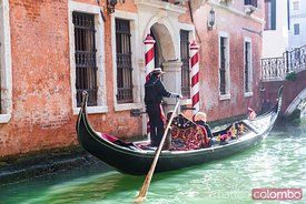 Gondola with adult couple of tourists on a canal, Venice