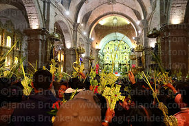 People holding crosses and ornaments made out of palm leaves inside San Francisco church during mass on Palm Sunday, La Paz, Bolivia
