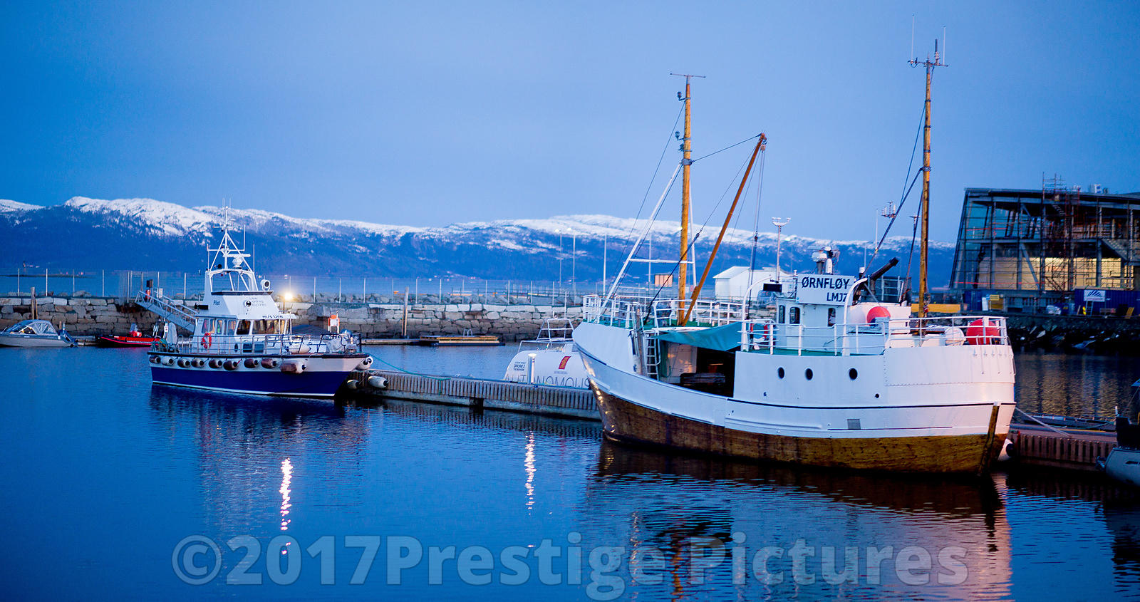 Boats in the Marina in Trondheim with snow Capped Mountains Behind - Norway The Monte-Carlo Historique Rally 2018 - Banbury royalty free stock photo library