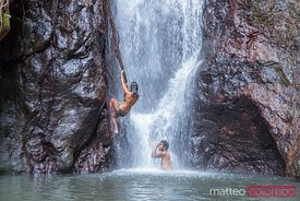 Woman climbing on the side of a waterfall in an island, Fiji
