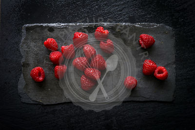 Wet raspberries on black slate board. Top view.