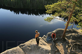 Climbers on top of a cliff by a lake