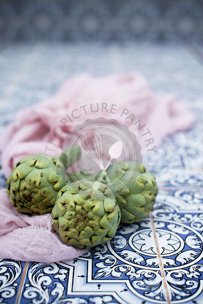 Artichoke heads on a tiles kitchen table