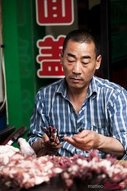 Man preparing meat skewers at the market, China