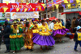 A pepino and cholitas dancing during parades for the Entierro del Pepino, La Paz, Bolivia