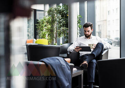 Businessman sitting in lobby, drinking coffee, using laptop