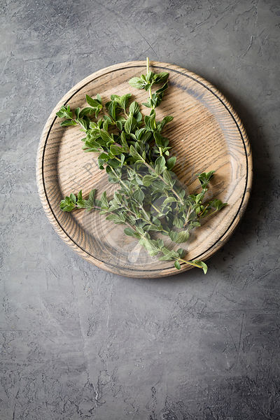 Fresh oregano on a wooden plate